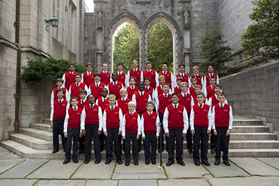 The American Boychoir standing on steps in front of a gothic archway.